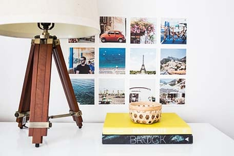 Grid of images on a wall with books on a table in front and lamp to the side Photo 7 – Close up of grid of images