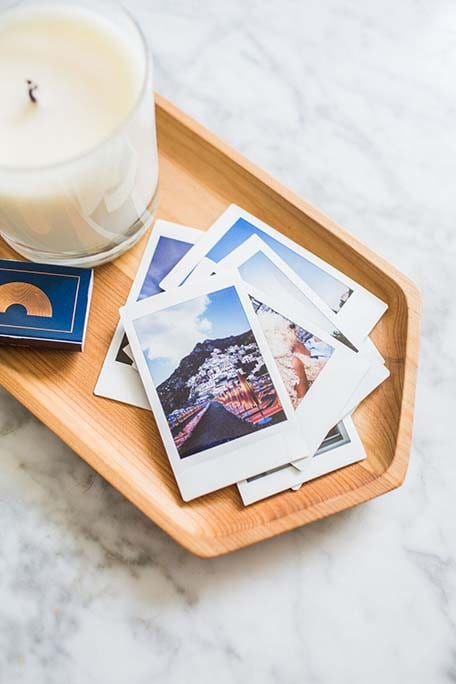 Close up of candle, matches and instant prints in wooden dish
