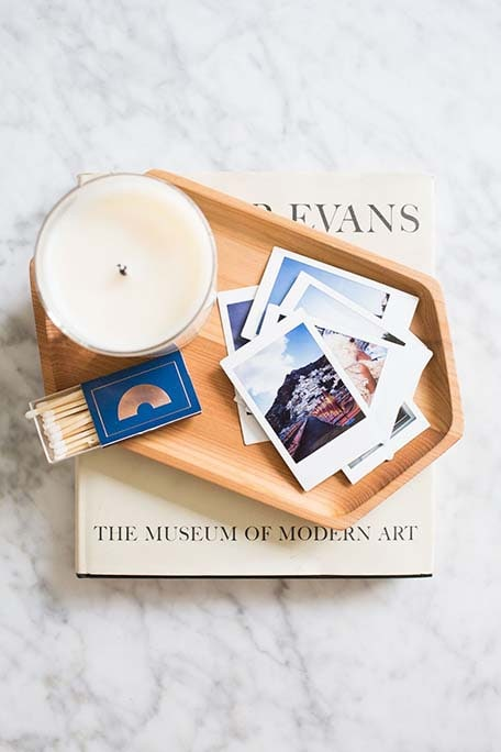 Overhead photo of candle, matches and instant prints in little wooden dish