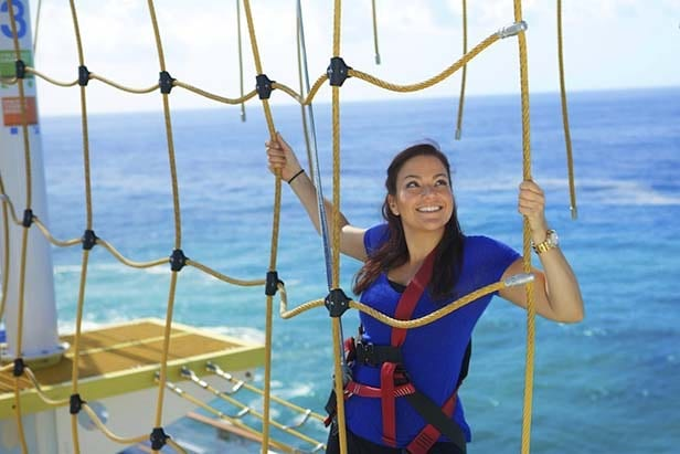 a woman goes through the ropes course at skycourse