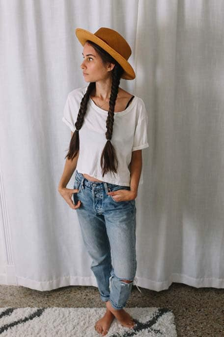 Drea looking to the side with her hair in fishtail pig tails and wearing a brown hat