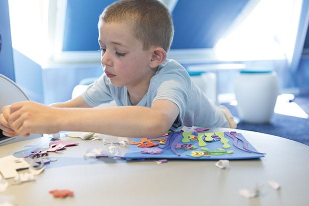 young boy enjoying arts and crafts on a carnival cruise