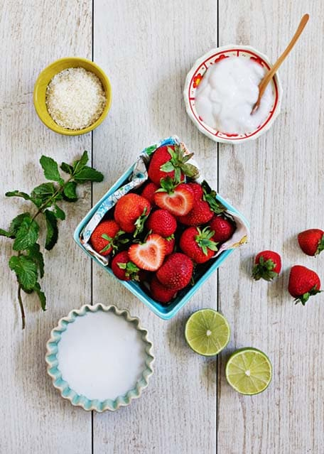 Strawberries, limes, coconut milk, coconut yogurt, mint leaves and salt on wooden table