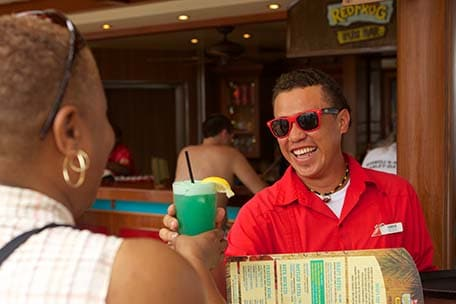 bar waiter delivers fruity drink at redfrog rum bar