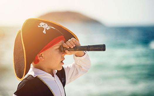 young boy in pirate costume looking through a spyglass
