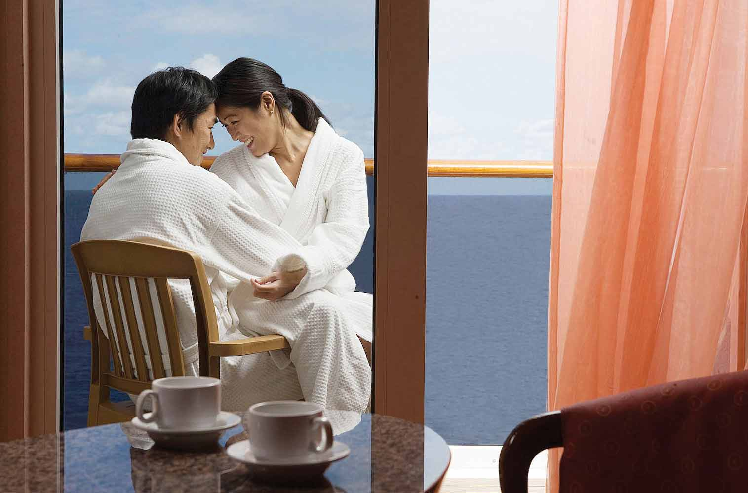 couple on a stateroom balcony in robes