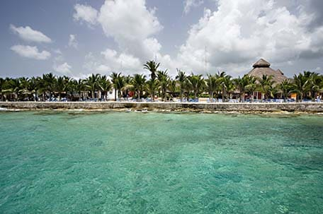 Clear blue water in Cozumel with the beach and palm trees in the distance