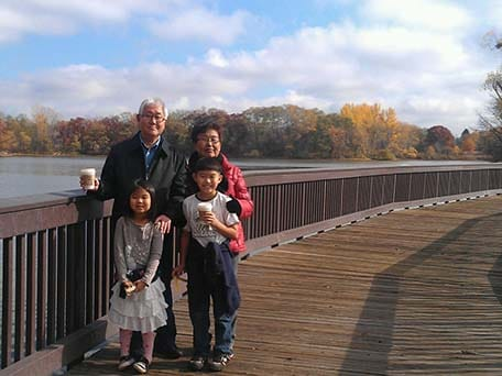 2 children with their grandparents standing on a bridge with water behind them