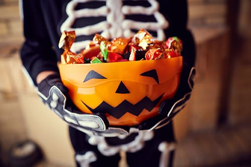 young boy in a skeleton costume holding bowl full of candy