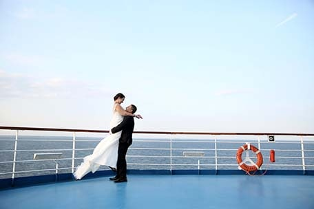 groom lifting his bride in the air on a carnival ship deck