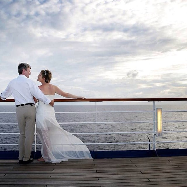 wedding couple looking at the sunset from their cruise ship