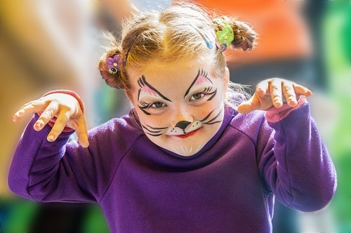 little girl paints her face to look like a cat during halloween