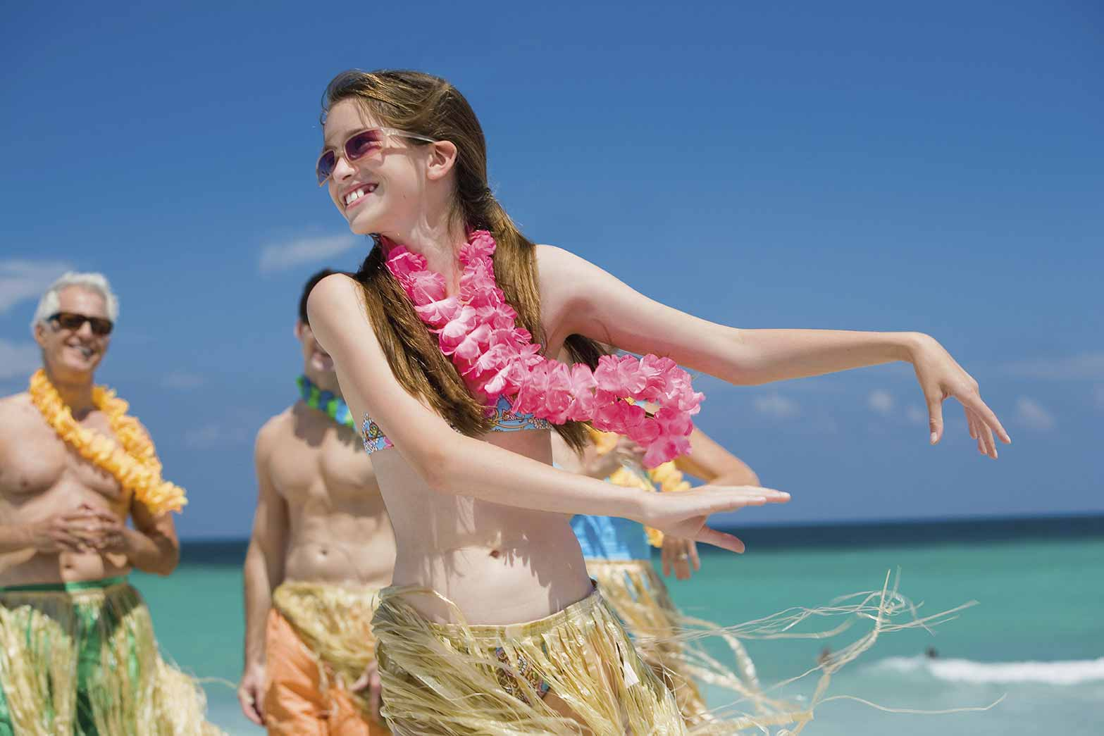 girl dressed as a hawaiian hula dancer on the beach