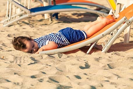 toddler dressed as a sailor sleeping on the beach