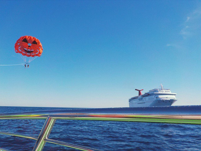 two people parasailing in Catalina island with a carnival cruise ship in the background
