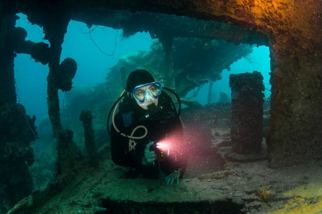 man scuba diving into a shipwreck in barbados