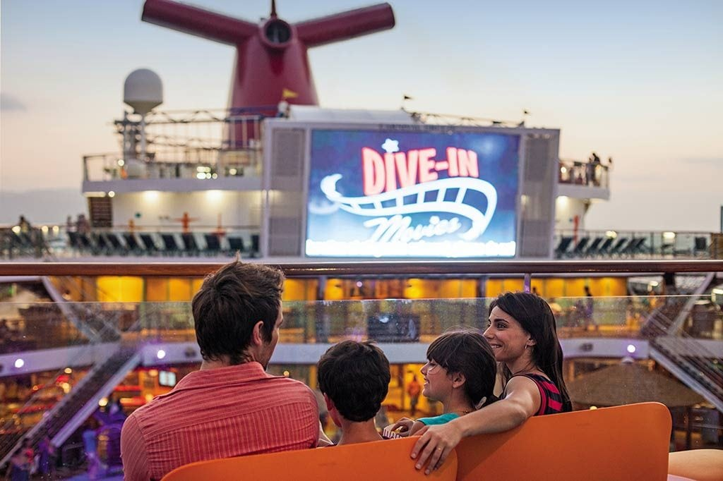 family sits on a carnival cruise deck and enjoys watching the seaside theater