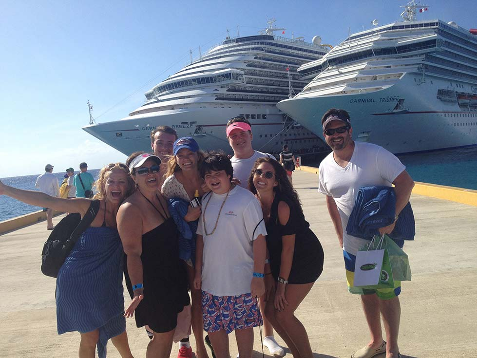 a family standing on a pier with two carnival ships docked in the background