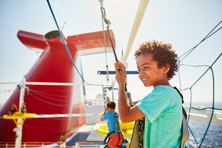 kid enjoying the view as he rope climbs on a carnival cruise
