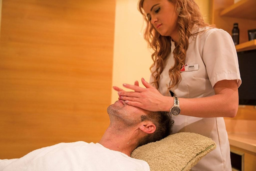 an receiving a face massage at the spa on a carnival cruise