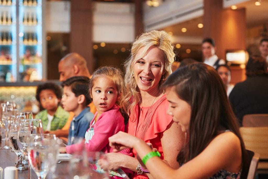 mother enjoying thanksgiving dinner with her daughters on a carnival cruise