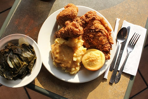 plate of fried chicken, mashed potatoes, corn bread and collard greens on the side
