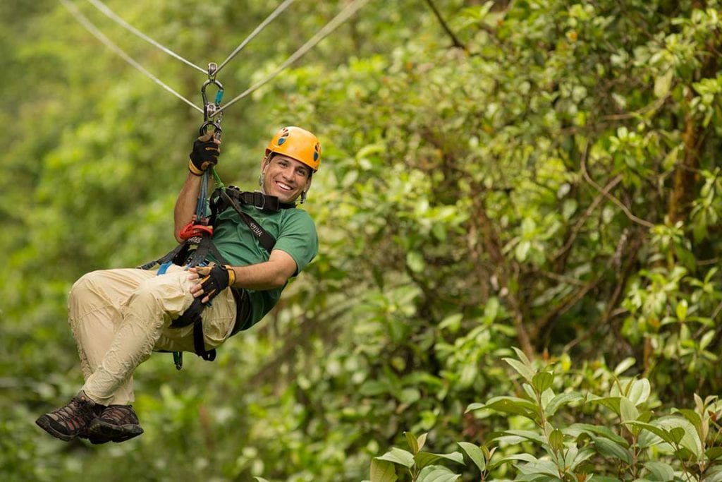 man zip lining through the forest in st kitts