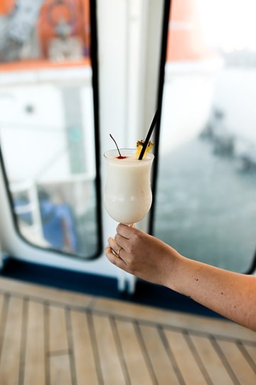 holding a pina colada while on board a carnival cruise