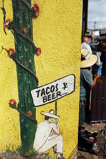 drawing of man wearing a sombrero holding a tacos y beer sign while sitting next to a cactus