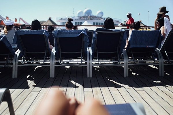 group of women sitting on beach chairs on the deck of carnival imagination