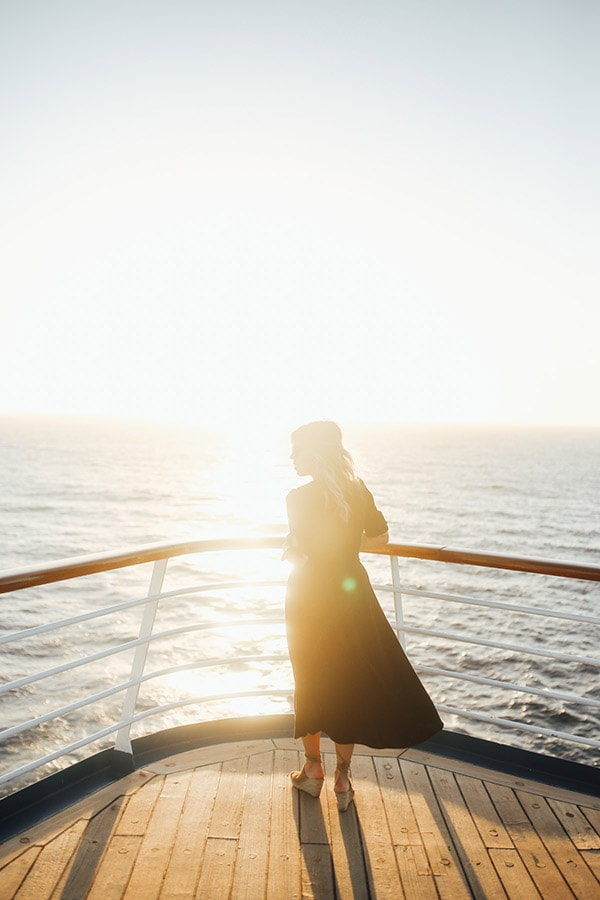 woman posing on a cruise deck as the sun rises in the background
