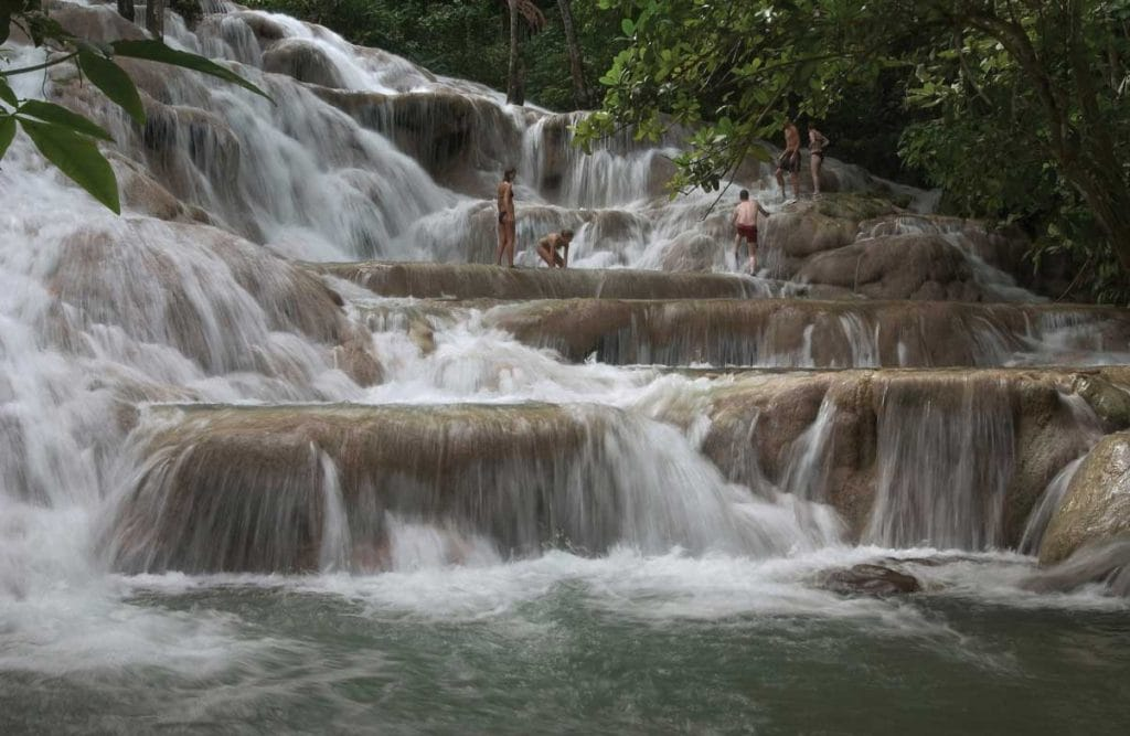 visitors climbing dunn's river in jamaica