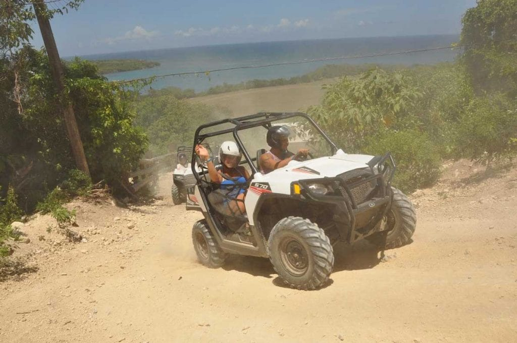 couple having fun riding an atv buggy up a hill in montego bay