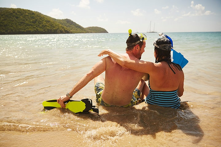 a couple sitting on a beach with snorkel gear