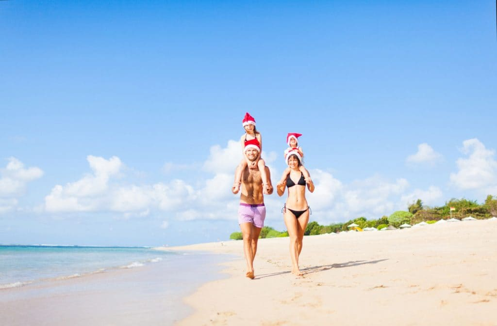 children on their parents' shoulders wearing santa hats while walking on a beach