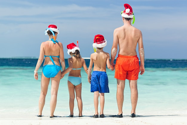 a family standing on a beach holding hands wearing santa hats