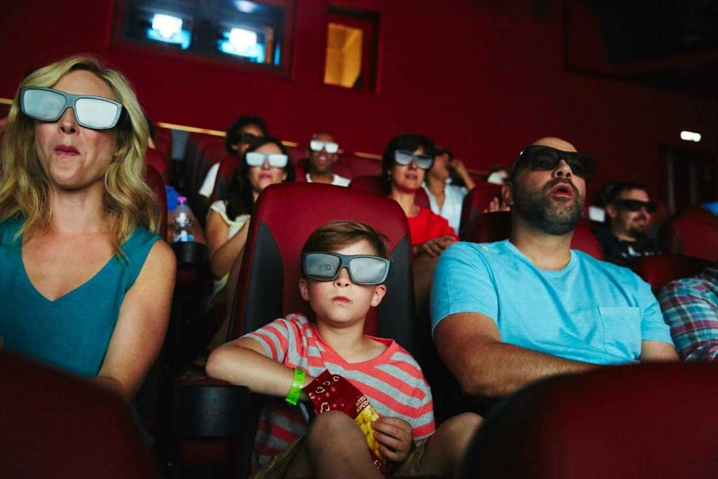 a family watching a movie at imax theater on board carnival horizon
