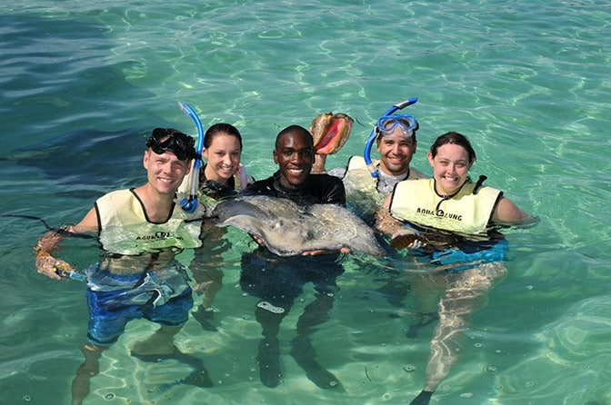 people standing in the ocean around a trainer holding a stingray in stingray cove