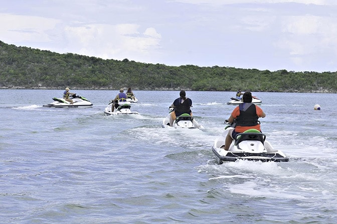 group of people riding aqua trax watercrafts in half moon cay