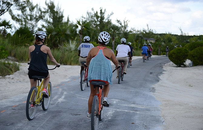 small group of people riding bicycles as they explore half moon cay