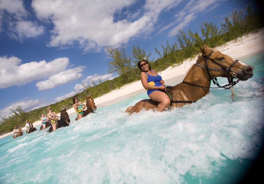 small group laughing as they ride through the ocean shore on horseback