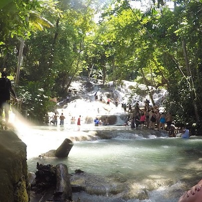large group hold hands as they climb up dunns river falls