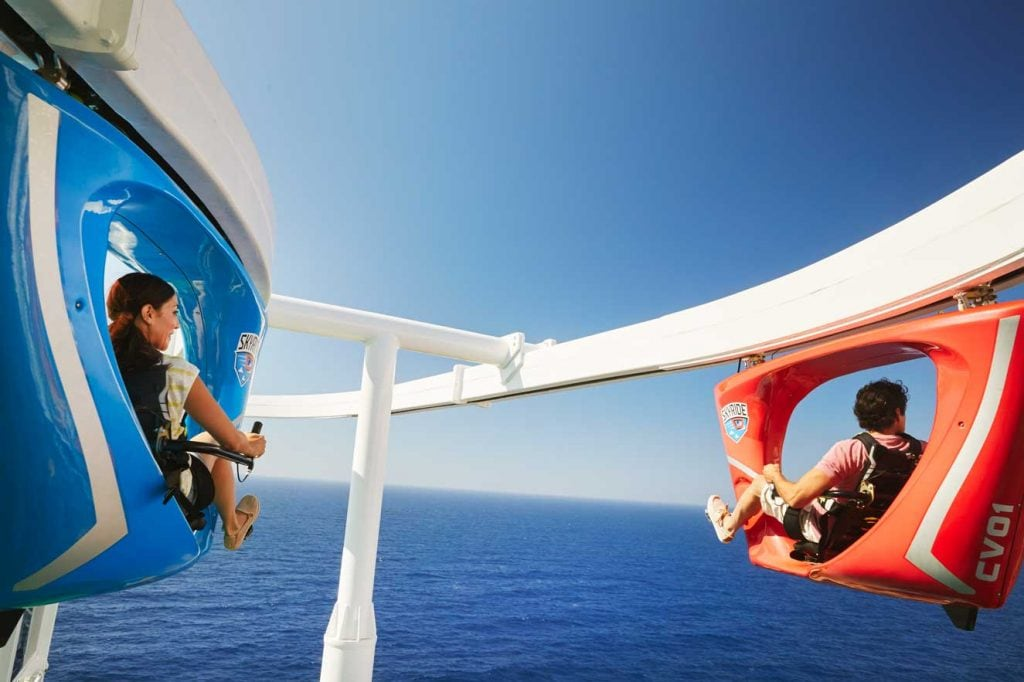 a man and woman staring at the ocean as they ride skyride on carnival horizon