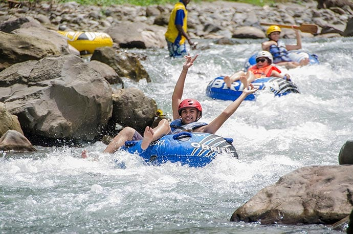 man raising his hands as he river tubes along the layou river while other guests follow behind him