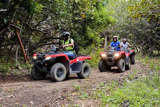 3 men riding an atv through the hidden trails in amber cove