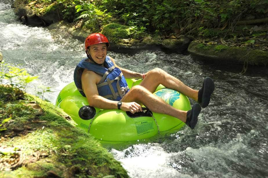 man laughing as he river tubes through white river