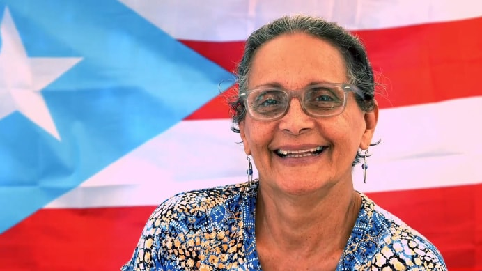 a senior puerto rican lady smiling in front of the puerto rican flag