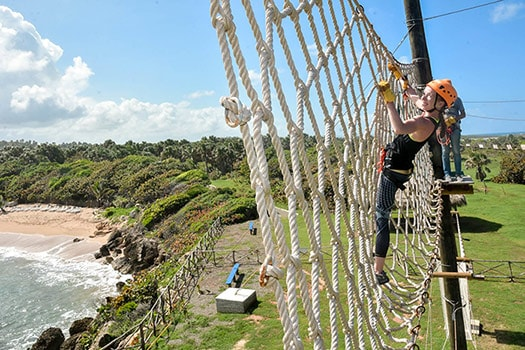 woman going through a rope bridge as she completes the challenge course in amber cove
