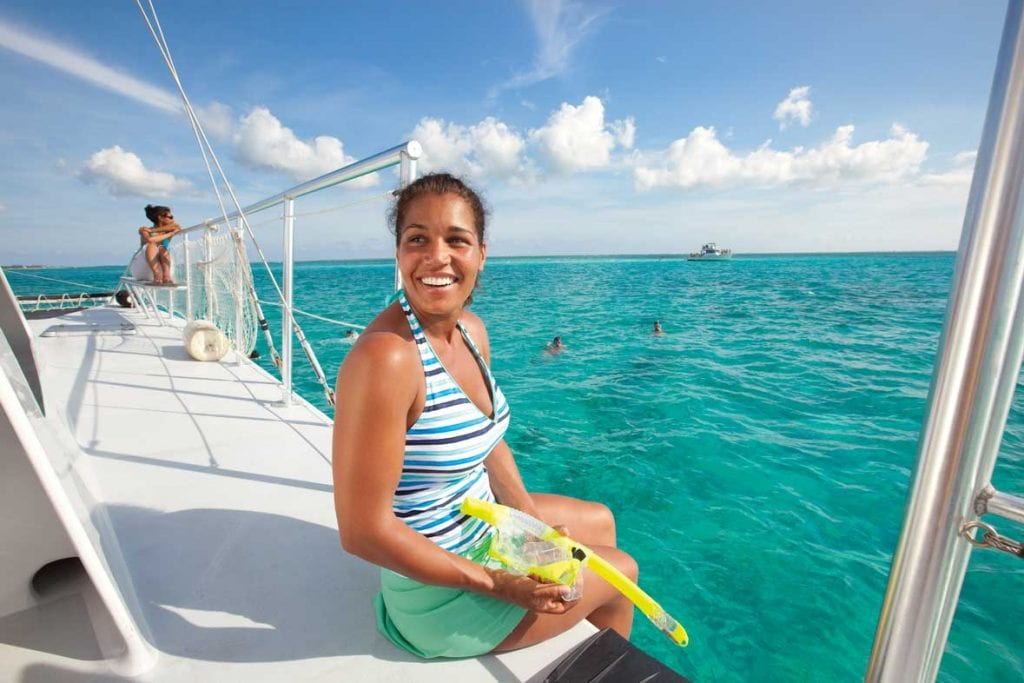 woman smiling while onboard a catamaran getting ready to snorkel