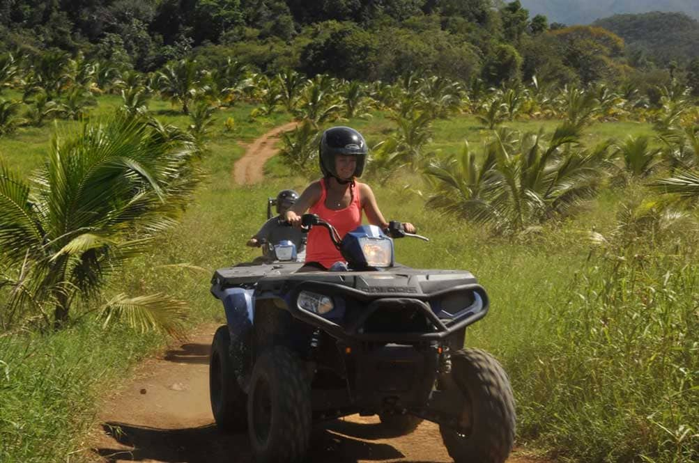 woman with a helmet riding an atv on dirt trails in ocho rios